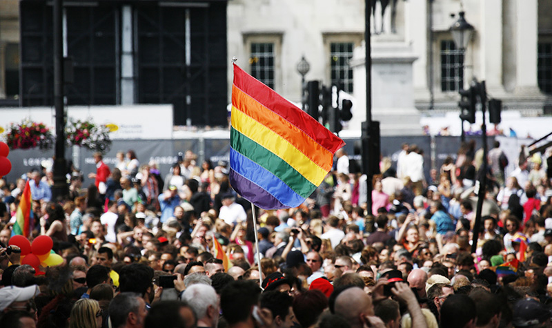 A crowd of people looking serious outside a building and a Pride Flag waving above them all.