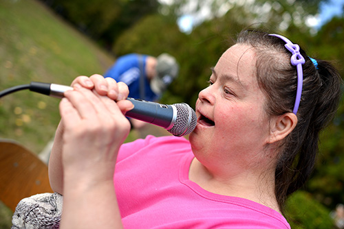 Woman with Down's Syndrome in pink shirt speaking into a microphone.