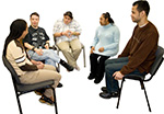 Five people with disabilities sitting on chairs in a circle having a conversation