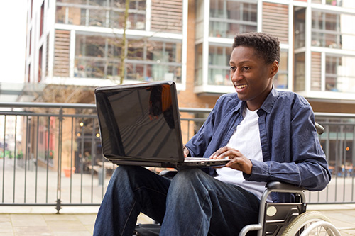 Young man in a wheelchair using a laptop outside.